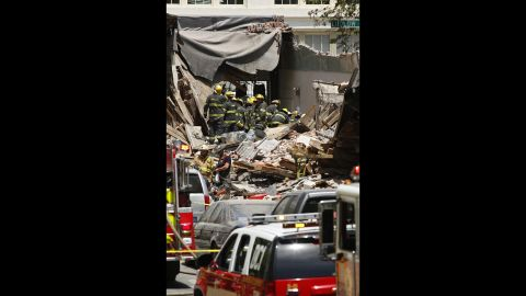 Emergency personnel work to pull a survivor from the rubble.