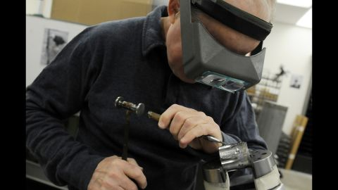 Jan Gwinnell uses a tiny hammer to engrave an intricate design onto the cylinder of a Colt revolver in the custom design shop at Colt Manufacturing Company's headquarters in West Hartford, Connecticut.