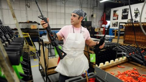Sergio Pereira adds a completed Colt rifle to a rack of guns.