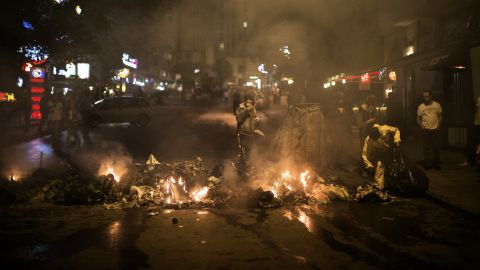 A municipal worker collects garbage set on fire by Turkish protesters in a restaurant district of Ankara on June 5.