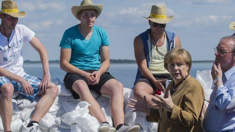 German Chancellor Angela Merkel and Reiner Haseloff, right, premier of the German state of Saxony-Anhalt, speak with volunteers about building a sandbag barrier near Lake Goitzsche in Bitterfeld-Wolfen, Germany, on June 6.