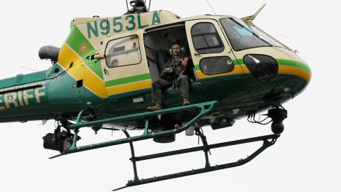 A Los Angeles County SWAT team sharpshooter circles the campus in a helicopter.