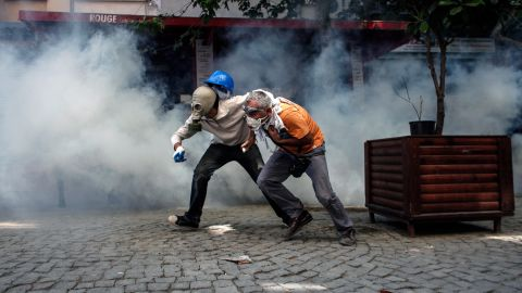 Protesters try to run from riot police on June 11.