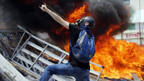 A protester uses a slingshot to throw stones at riot police on June 11.