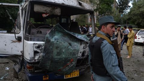 An Afghan policeman stands guard in front of a badly damaged bus at the site of a suicide attack in Kabul on June 11, 2013.