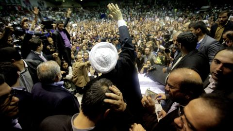 Hassan Rowhani (C), a moderate Iranian presidential candidate and former top nuclear negotiator, waves to his supporters as he attends his campaign rally in downtown Tehran on June 8, 2013.