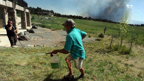Lynd Fitzgerald sprays fire retardant around a house in Colorado Springs on June 11.