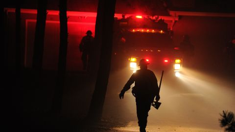 Firefighters from the Black Forest Fire Department race toward a burning home near Colorado Springs on June 11.