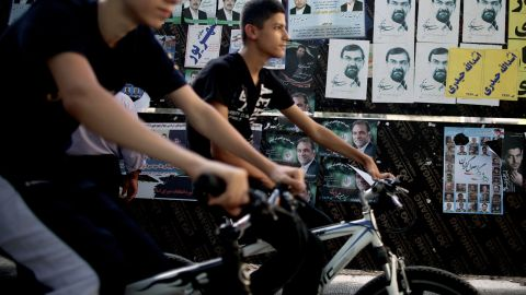 Youths ride past campaign posters in downtown Tehran on Thursday, June 13, a day ahead of the country's presidential election.