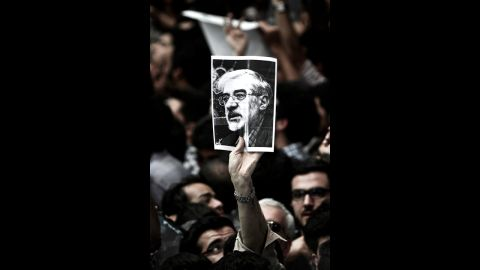"""A man holds a portrait of opposition leader Mir Hossein Mousavi, who has been <a href=""""http://www.cnn.com/2011/WORLD/meast/02/19/iran.opposition.leader/index.html"""">under house arrest since February 2011</a>, during a campaign rally for Aref in Tehran on June 10."""