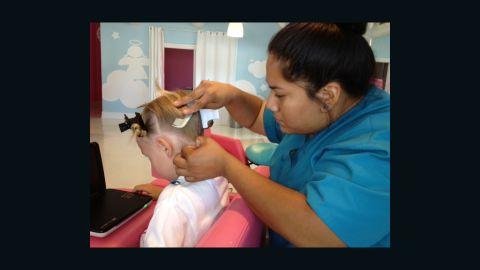 Poli Rodriguez removes a nit from 9-year-old Emma's hair at a Pasadena, California, salon.