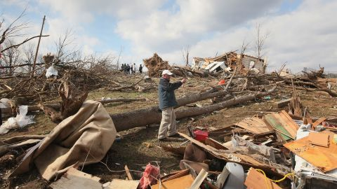 Insurance adjuster Mark Ricketts photographs a home destroyed by a tornado in Henryville, Indiana, on March 4, 2012. Tornadoes and severe weather that struck the Ohio valley and southeast on March 2 and March 3 caused about $3.1 billion in losses.