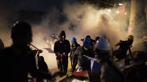 Protesters scramble for safety as Turkish riot police officers push them out of Gezi Park using tear gas and rubber bullets.