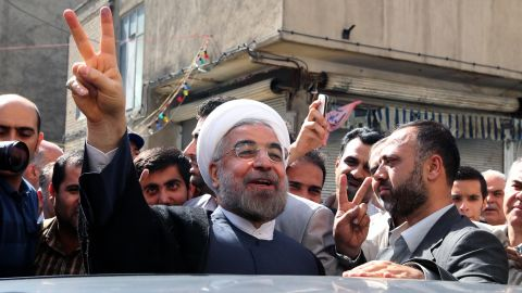 Iranian presidential candidate, Hassan Rouhani flashes a victory sign as he leaves a polling station after voting in Tehran on June 14, 2013.