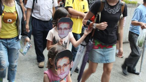 """Ruth Jopling brought her daughters, Amber, 8, and Jade, 3, to the protest, who held cut-out masks on sticks bearing Snowden's image.  """"It's not just about our generation, but the next generation as well,"""" Jopling said.  Amber echoed her mother's sentiment: """"When I grow up, I can tell my children about this."""""""