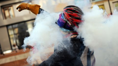 A protester throws a tear gas canister back at riot police during clashes near Taksim Square on June 16.