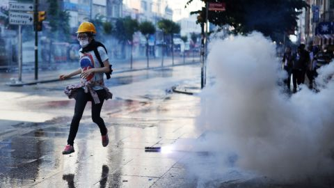 A protester runs during clashes between riot police and demonstrators in the streets adjacent to Taksim Square in Istanbul on Sunday, June 16.