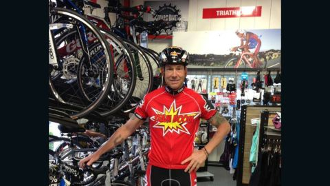"""Dave Nazaroff in his bike shop in a """"Team Boom"""" T-shirt he and his wife designed for the charity bike ride."""