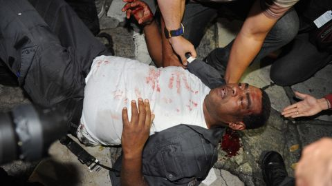 A riot police officer receives help after clashing with protesters on June 17.