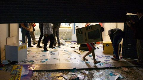 An unidentified person carries a television out of a store in Sao Paulo on June 18.