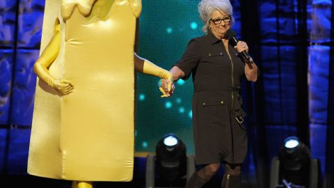 """Deen on stage with a costumed Kevin Bacon at Comedy Central's """"Night of Too Many Stars: America Comes Together for Autism Programs"""" in 2012 in New York."""