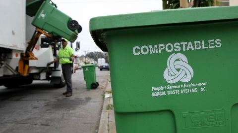 Manuel Vera dumps a bin with compostable materials into a truck while collecting recyclable materials in San Francisco.