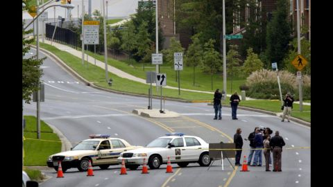 A stretch of road where 40-year-old bus driver Conrad Johnson was shot and killed is blocked off in Aspen Hill, Maryland, on October 22, 2002. Johnson was the last victim of the Beltway sniper attacks.