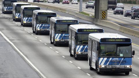 A motorcade of buses bearing the name of driver Conrad Johnson, the last victim of the three-week shooting rampage, travels on the Beltway to Johnson's funeral in Washington on October 26, 2002.