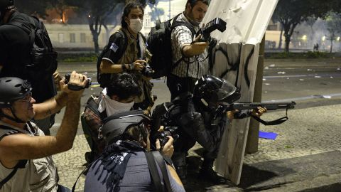 Photographers wait for a riot police officer to fire rubber bullets on June 20 in Rio de Janeiro.