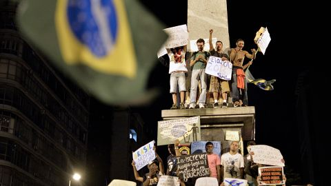 Protesters shout from a statue in Belo Horizonte, on June 20.