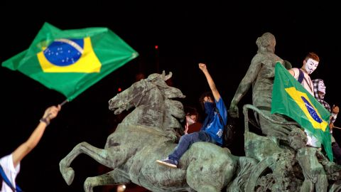 Demonstrators stand on a statue in Niteroi outside Rio de Janeiro on Wednesday, June 19.