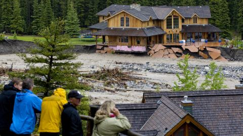 Residents watch as floodwaters from Cougar Creek destroy a neighborhood in Canmore, Alberta, on Thursday, June 20.
