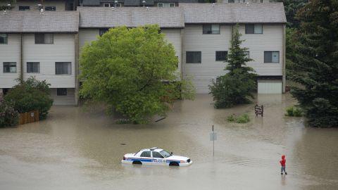 A woman walks toward an abandoned and partially submerged police car in Calgary's Sunnyside neighborhood on June 21.