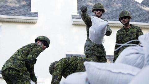 Canadian Armed Forces soldiers from the Calgary Highlanders pile sandbags to protect the Inglewood neighborhood in Calgary on June 22.