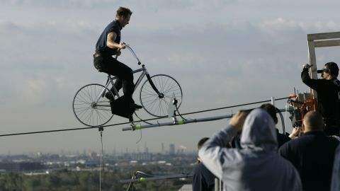 """Wallenda pedals to the end of a wire 12 stories above a Newark, New Jersey, street in October 2008. He earned the <a href=""""http://www.worldrecordacademy.com/stunts/highest_and_longest_bike_ride-Nick_Wallenda_sets_world_records_80407.htm"""" target=""""_blank"""" target=""""_blank"""">Guiness World Record</a> for the longest distance and greatest height traveled by bicycle on a high wire when he traveled 235 feet at a height of 135 feet."""