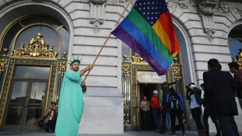 A gay rights supporter waves a flag outside City Hall in San Francisco ahead of the Supreme Court decisions on June 26.