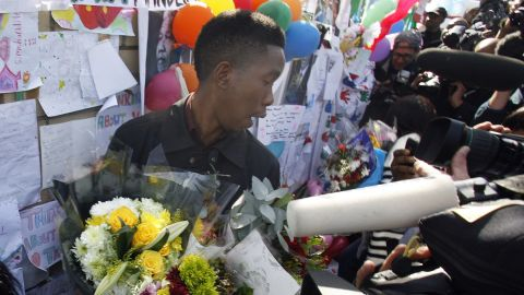 A member of Mandela's family is swamped by the media on June 27 while collecting flowers from well-wishers.