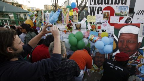 Supporters view and photograph get-well messages and other mementos placed on a fence near the hospital on June 27.