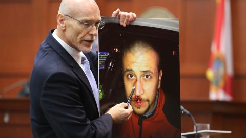 """Defense attorney Don West displays a photo of Zimmerman from the night of the shooting during his opening arguments on June 24. He opened his statements with a knock-knock joke but failed to win a laugh. """"Knock knock. Who's there? George Zimmerman. George Zimmerman who? Good, you're on the jury,"""" he said."""