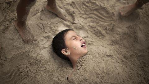 R.J. Hernandez, 8, of El Campo, Texas, is buried in sand as he tries to stay cool in Santa Monica on June 28.