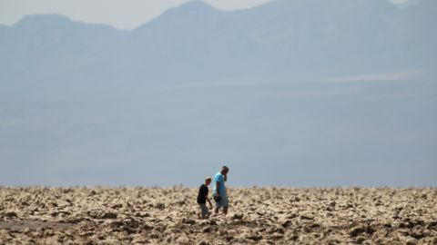 """People walk through the """"Devil's Golf Course"""" area of Death Valley, where temperatures were 116 degrees."""