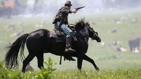 A Confederate Civil War cavalry reenactor shoots at Union soldiers during Pickett's Charge on the last day of a Battle of Gettysburg reenactment on Sunday, June 30, during 150th anniversary celebrations in Gettysburg, Pennsylvania. More than 10,000 reenactors will pay tribute to the major clashes that took place in the pivotal Civil War battle in July 1863.