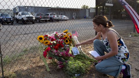 Toby Schultz lays flowers on July 1 at the fence of the fire station in Prescott, Arizona, the home base of 19 firefighters who died in the Yarnell Hill Fire.