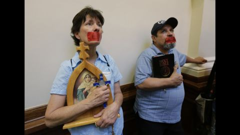 """Anti-abortion demonstrators taped the word """"life"""" over their mouths as they stood in the rotunda of the state Capitol in July 2013."""