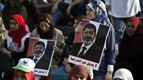 Egyptian supporters of President Mohamed Morsi hold posters bearing his portrait during a rally outside Cairo University on June 3, 2013. Egyptian security forces imposed a travel ban on President Mohamed Morsi and several top Islamist allies over their involvement in a prison escape in 2011, security officials said. AFP PHOTO / KHALED DESOUKIKHALED DESOUKI/AFP/Getty Images