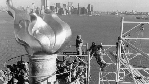 Workers remove scaffolding from around the statue's torch after restoration work in 1985.