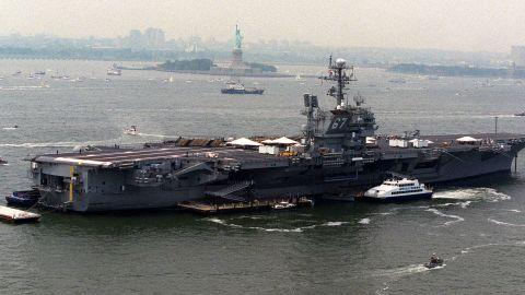 The aircraft carrier USS John F. Kennedy is anchored in New York Harbor near the Statue of Liberty in 2000.