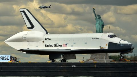 The Space Shuttle Enterprise passes the statue while being towed on a barge in June 2012.