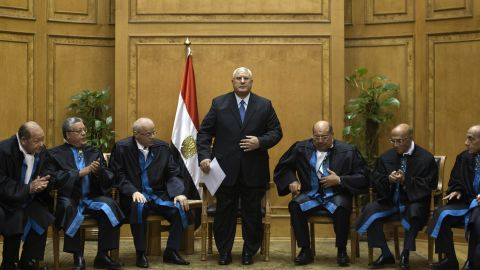 Adly Mansour, center, stands after delivering a speech during his swearing-in ceremony as Egypt's interim president in the Supreme Constitutional Court in Cairo on July 4. Mansour has served as the head of the country's Supreme Constitutional Court.