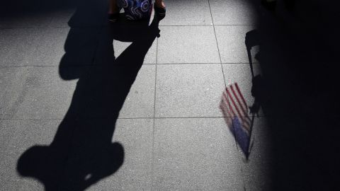 An American flag casts a shadow on the ground as spectators wait for a public reading the Declaration of Independence in Boston.